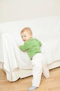 Kind lernt laufen und hält sich fest