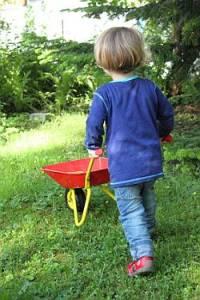 Kind läuft mit Schubkarre