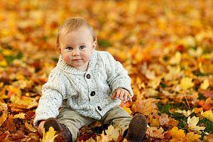 Bild: Baby sitzt im herbstlichen Laub